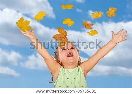 Happy shouting little girl welcoming the falling autumn leaves against cloudy sky - stock photo