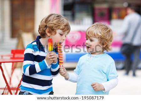 Happy sibling boys: Two kids feeding each other with ice cream