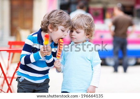 Happy sibling boys: Two kids feeding each other with ice cream - stock photo