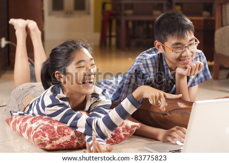 happy sibling, sister and brother laughing with game in computer notebook. - stock photo