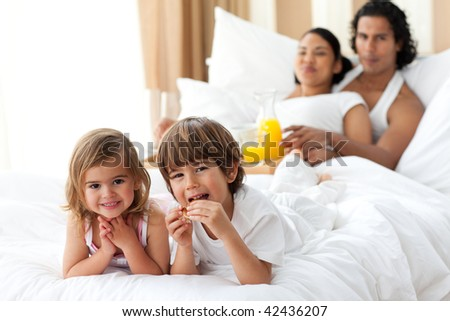 Happy siblings having breakfast with their parents lying on the bed