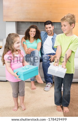 Happy siblings holding presents in front of parents on the couch at home in living room - stock photo
