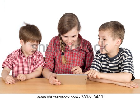 Happy Siblings Sitting at the Desk and Using Tablet, Half-Length Studio Shot Isolated on White - stock photo