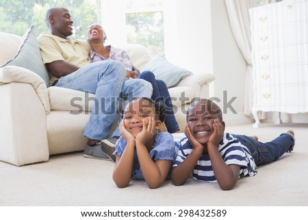 Happy siblings sitting on the floor watching television at home in the living room