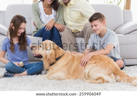 Happy siblings stroking dog while father and mother sitting on sofa at home - stock photo