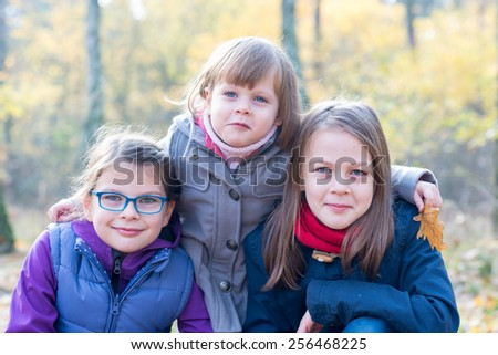 Happy Siblings - Three sisters in the autumnal forest smiling and hugging - stock photo