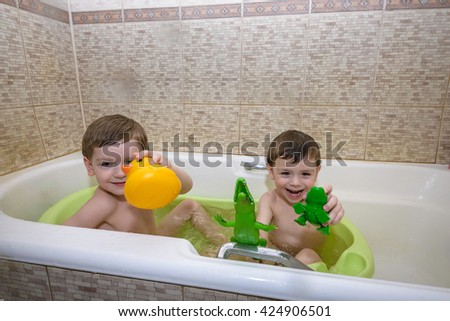 Happy siblings: Two little twins children playing together with water by taking bath in bathtub at home. Kid boys having fun together. - stock photo