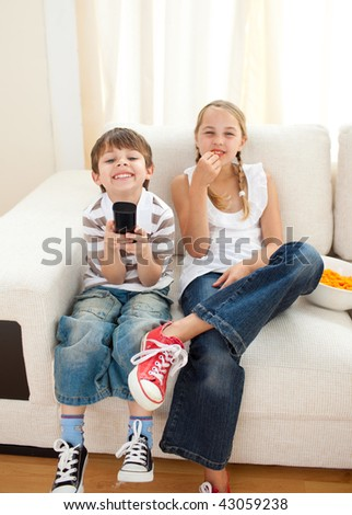 Happy siblings watching TV on the sofa