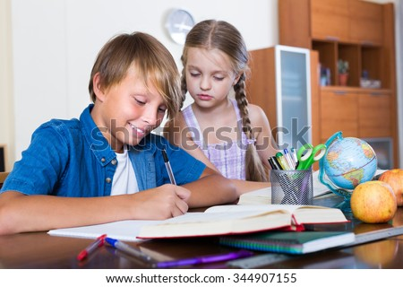 Happy siblings writing  homework with books and at home