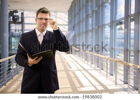 Happy single businessman holding folder, smiling at office lobby.