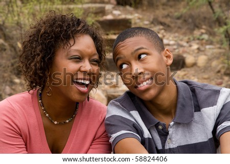 Happy single-parent and son laughing in an outdoor setting - stock photo