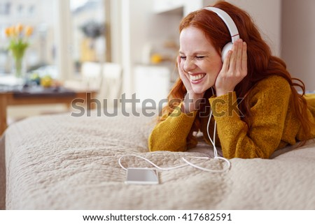 Happy single young woman in yellow sweater laying down on bed with eyes closed while listening to something enjoyable - stock photo