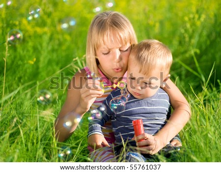 Happy Sister and Brother blowing soap bubbles