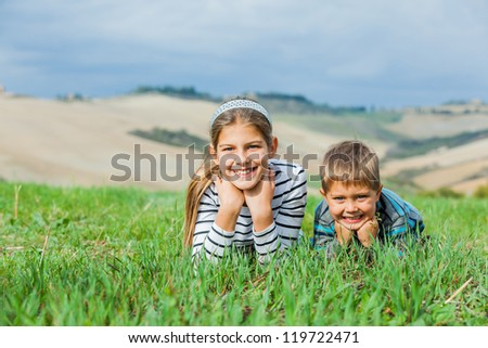 Happy sister and brother having fun on vacations in Tuscan against beautiful landscape background - stock photo