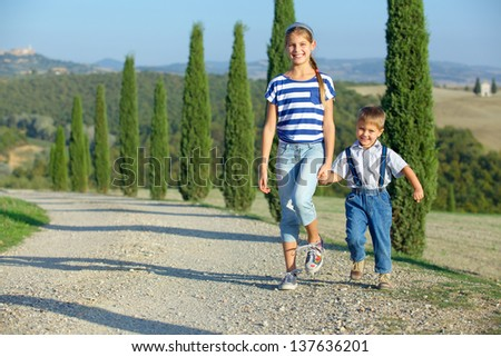 Happy sister and brother having fun on vacations in Tuscan against cypress alley background - stock photo