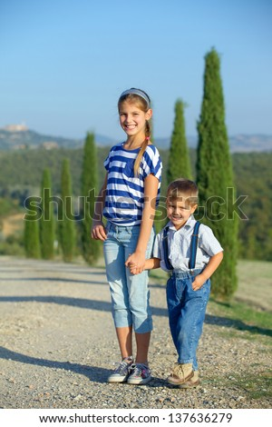 Happy sister and brother having fun on vacations in Tuscan against cypress alley background. Vertical view