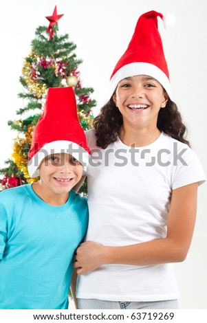 happy sister and brother in front of christmas tree - stock photo