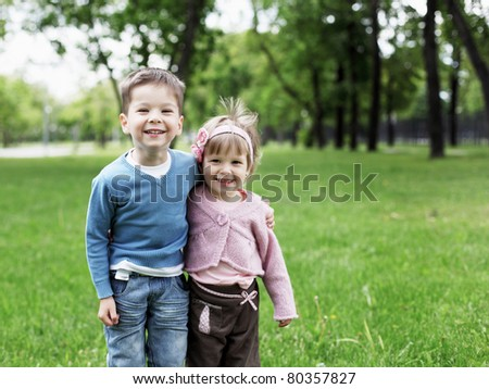 happy sister and brother together in the park - stock photo