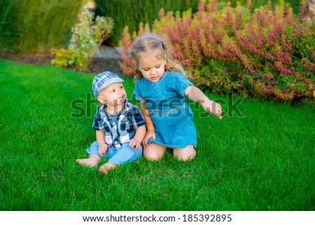 happy sister and brother together on the grass