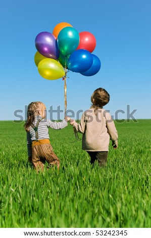 Happy sister and brother with balloons walking on the spring field - stock photo