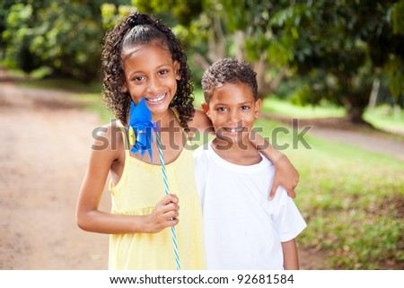 happy sister and brother with pinwheel outdoors