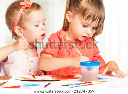 happy sister little girl in kindergarten draw paints - stock photo