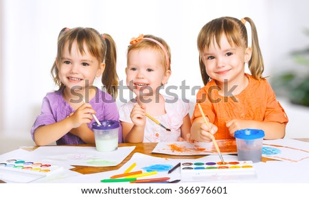 happy sister little girls in kindergarten draw paints - stock photo