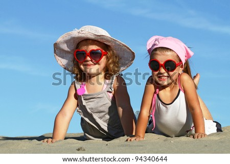 Happy sisters posing with sunglasses on the beach - stock photo