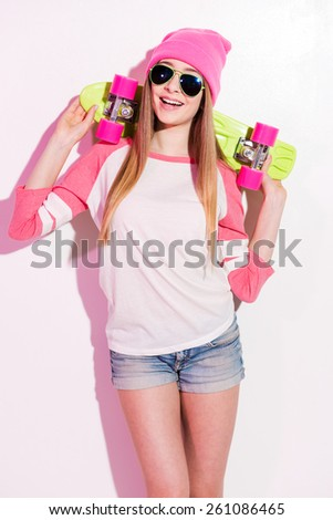 Happy skater girl. Playful young woman in pink headwear and sunglasses holding skateboard on her shoulders while standing against white background - stock photo
