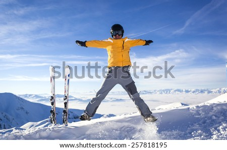 happy skier man jumping at the peak of mountain - stock photo