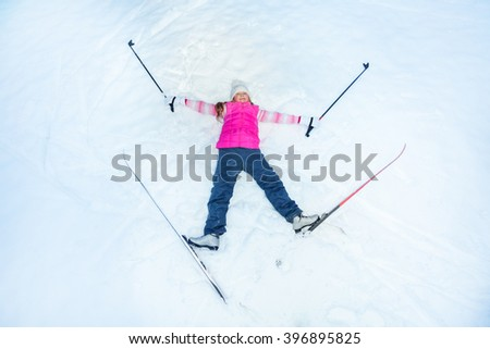 Happy skier with skis an sticks laying on the snow - stock photo