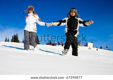 happy skiers hurry on snow - stock photo