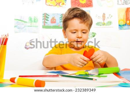 Happy small boy crafting heart shaped carton - stock photo