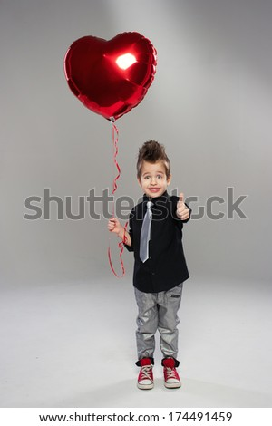 Happy small boy with red heart balloon on a light background  - stock photo