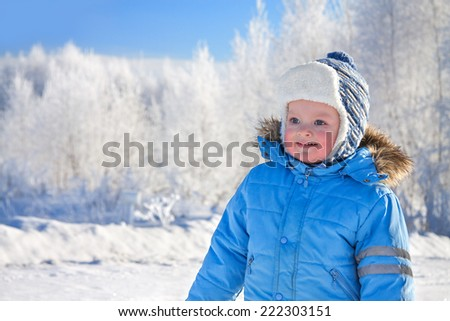 happy small child the boy on walk in the winter in park - stock photo