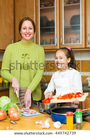 Happy small daughter helping mother to make soup at kitchen. Focus on the child - stock photo