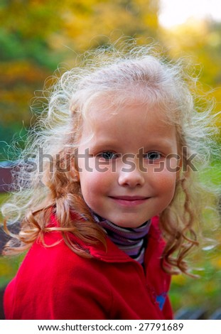 Happy small girl in golden autumn city park