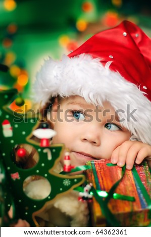 Happy small girl in santa hat with present have a christmas - stock photo