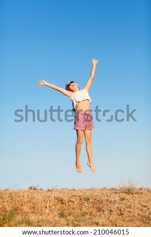 happy small girl jumping outdoors - stock photo
