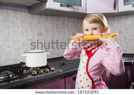 happy small girl with macaroni in the kitchen - stock photo