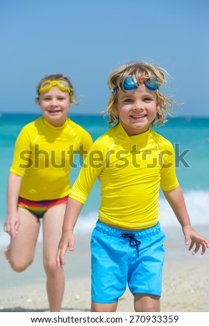 Happy small kids in swimming goggles having fun at a tropical beach - stock photo