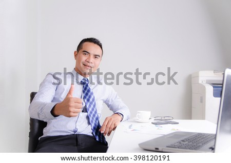 Happy smile asian business man showing thumb up with cheerful in work space - stock photo