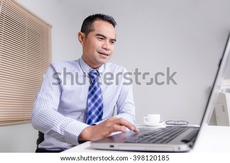 Happy smile business man using laptop computer in office