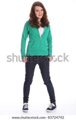 Happy smile from pretty teenager school girl with long brown hair, wearing dark blue jeans and a green sweater.