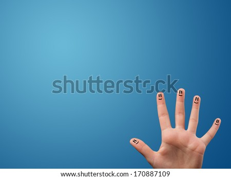 Happy smiley face fingers cheerfully looking at empty blue background copy space - stock photo