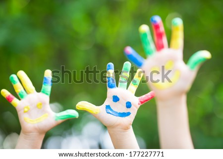 Happy smiley hands against green spring background - stock photo