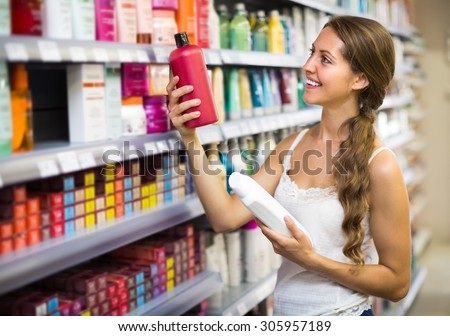 Happy smiling adult girl choosing shampoo at supermarket