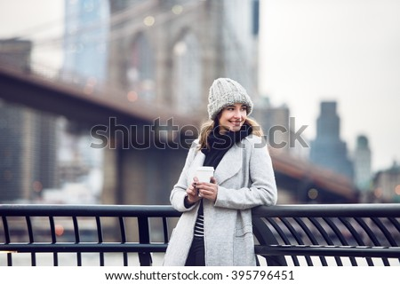 Happy smiling adult tourist woman holding paper coffee cup and enjoying the New York City view and Brooklyn bridge - stock photo