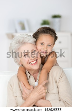 Happy smiling affectionate grandmother and her cute little granddaughter giving each other a loving hug as they smile at the camera - stock photo