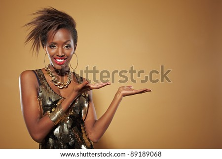 Happy smiling african woman presenting an imaginary product - stock photo